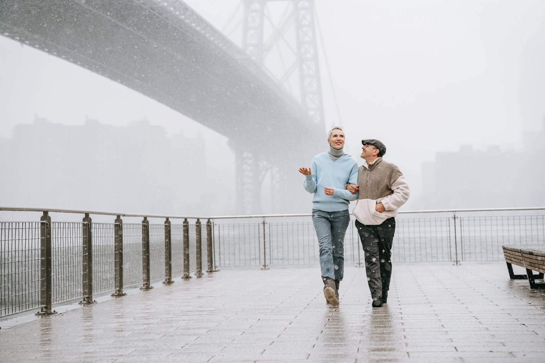 cheerful couple walking on embankment in snowy weather